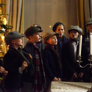 De leerlingen van de Broederschool worden in de Blauwe Kamer ontvangen waar ze zich opstellen rond een feestelijk opgetuigde kerstboom