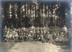 De weeskinderen die tijdens de Eerste Wereldoorlog op het domein van kasteel ter Gaever werden opgevangen, poseren met speeltuigen in het park. Archief de Bergeyck, collectie John Buyse